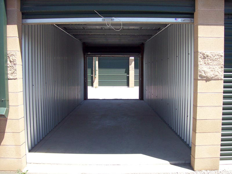 safe and secure self storage building from west side with parking lot and phone number